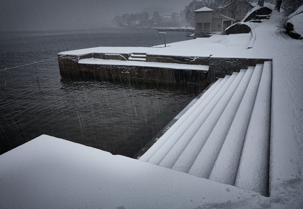 staircase covered in snow near body of water