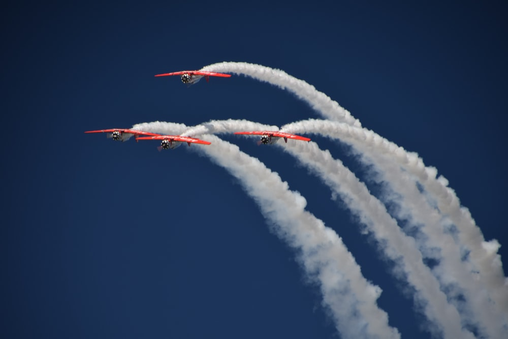 four red planes with contrails