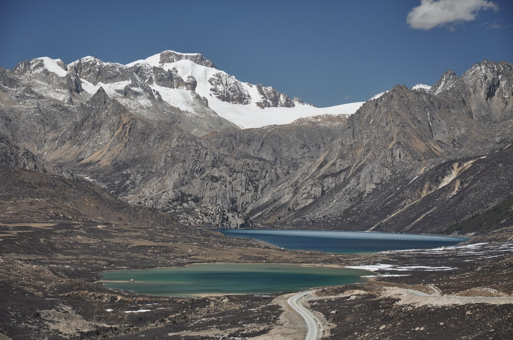 two lakes near road in distant of snow capped mountain