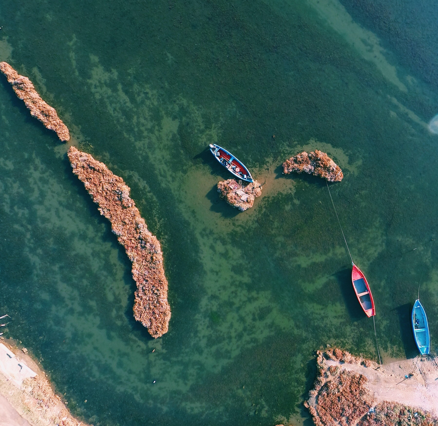 bird's-eye view photography of three assorted-color boats docked on white rocks