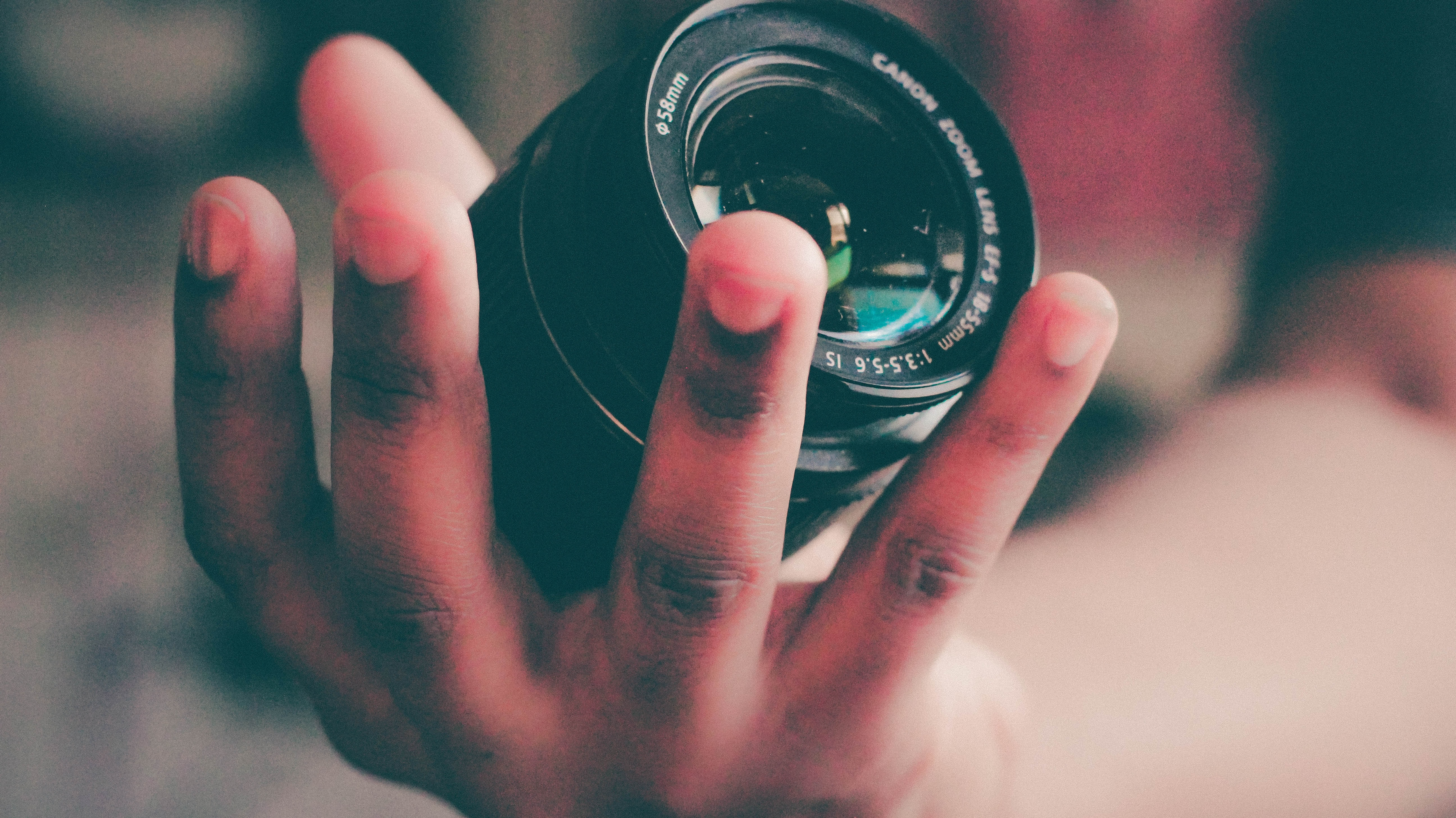 shallow focus photography of person holding black DLSR camera lens
