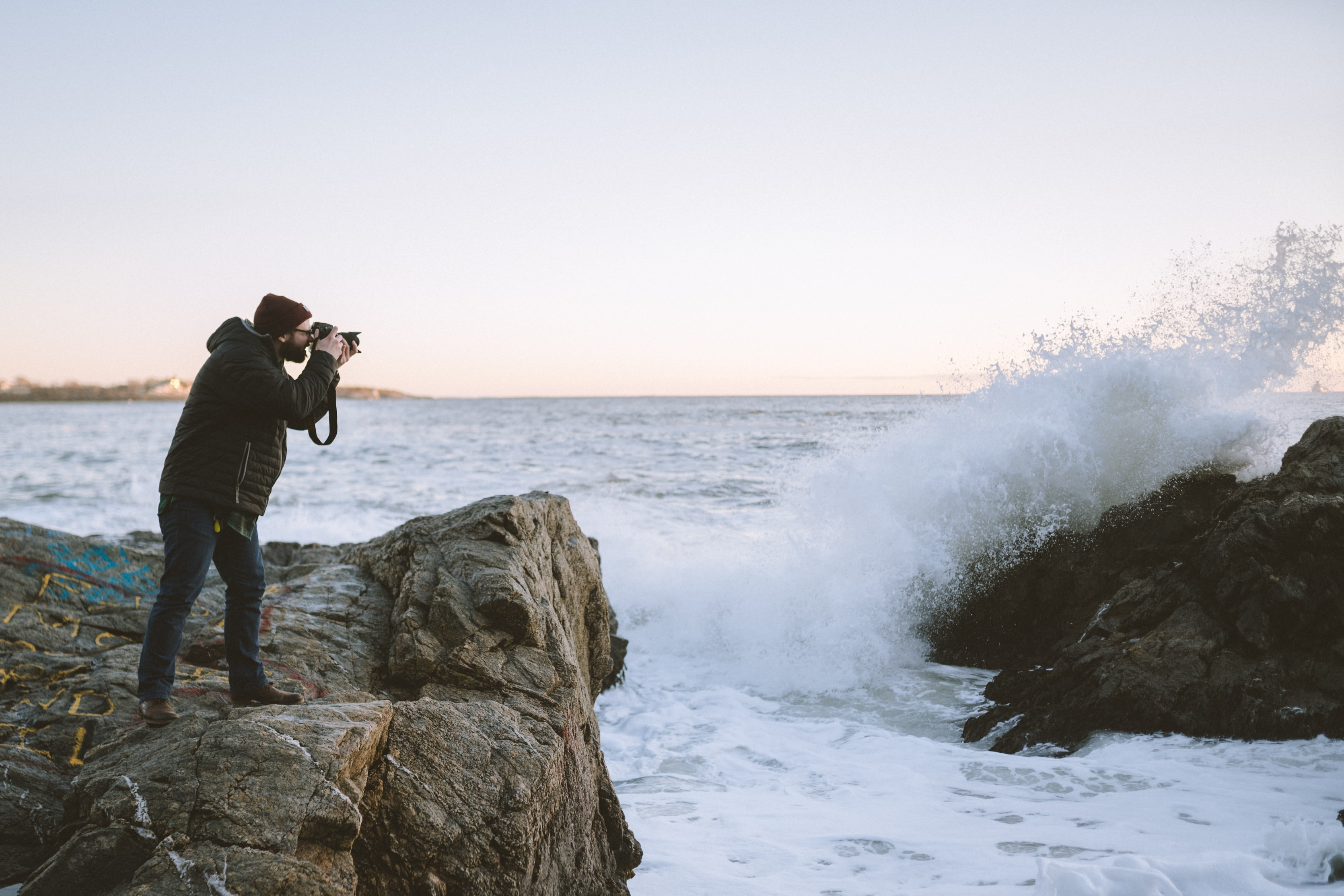 man taking photo of rock formation with sea waves at daytime