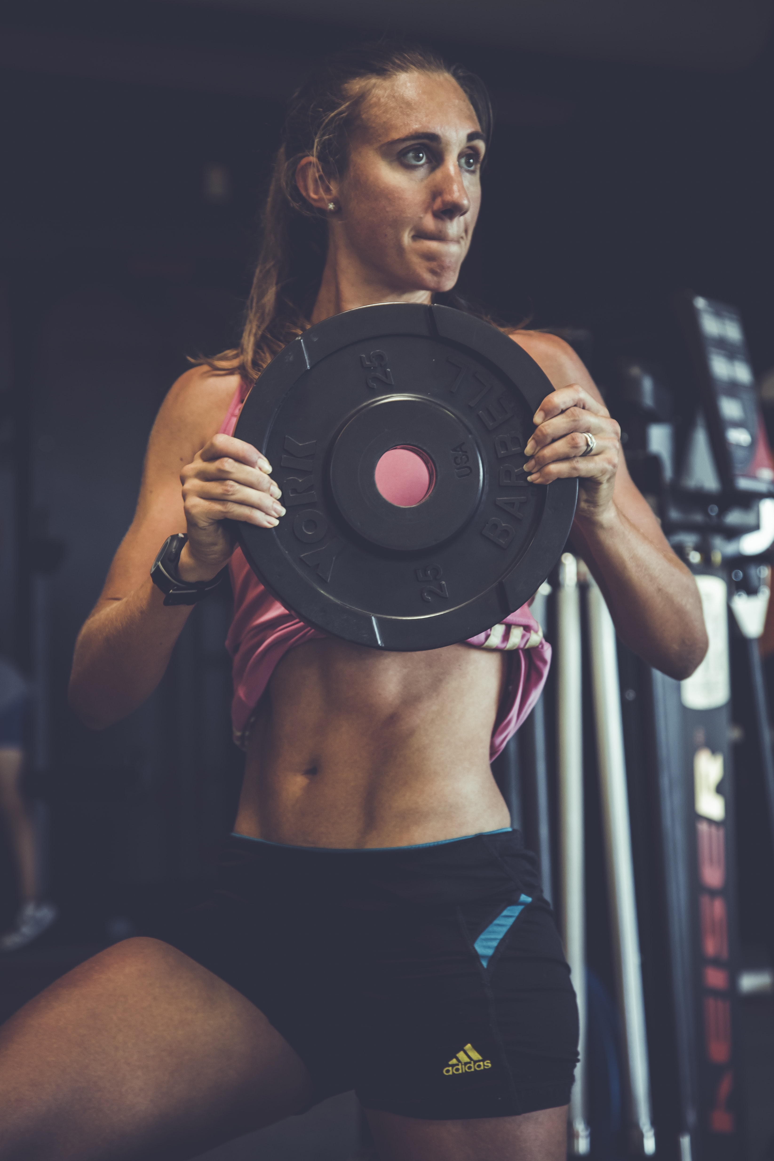 woman holding weight plate doing exercise