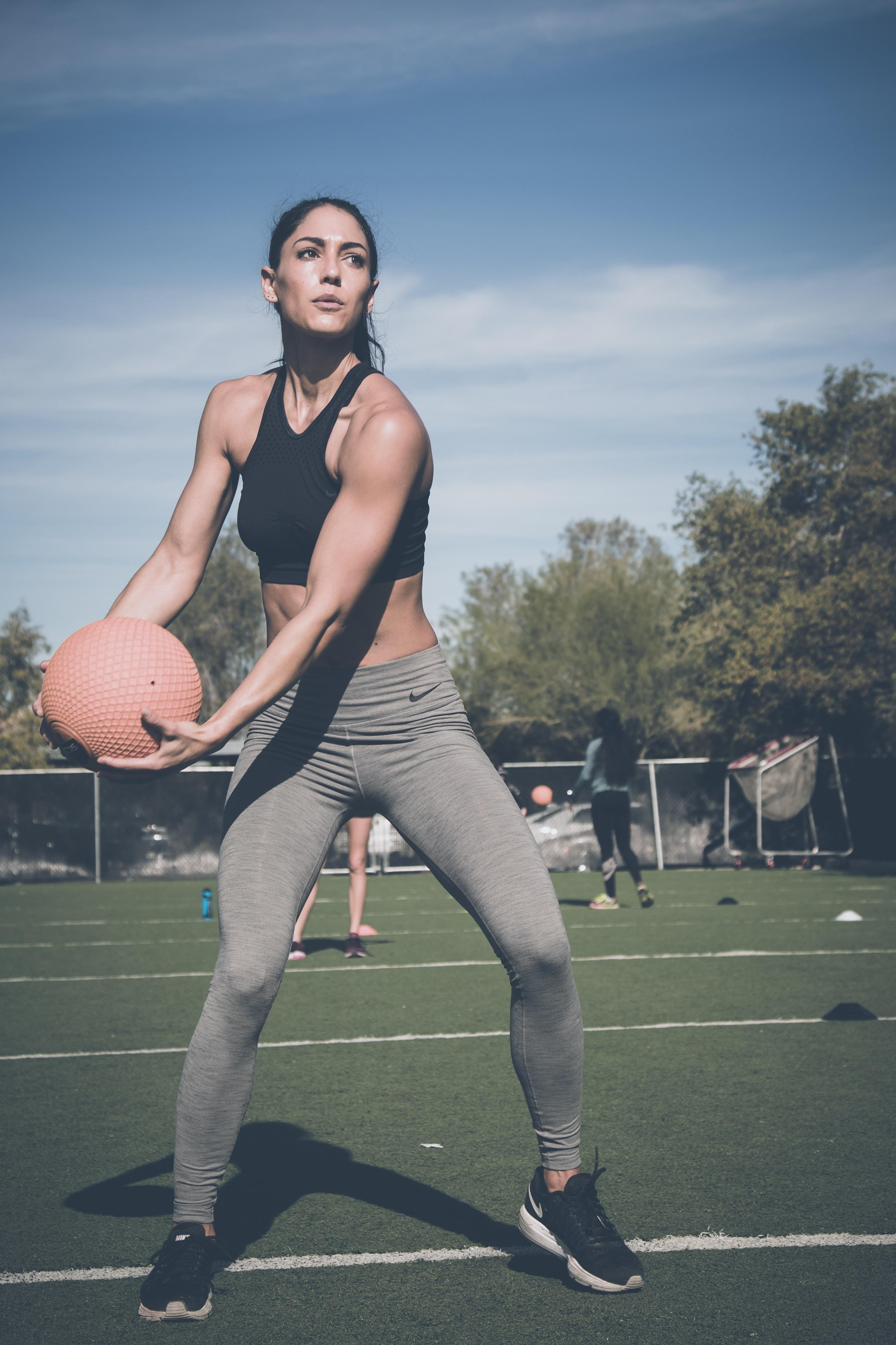 woman holding training ball under sunny sky