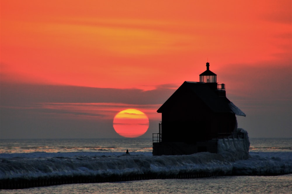 silhouette of house beside ocean during orange sunset