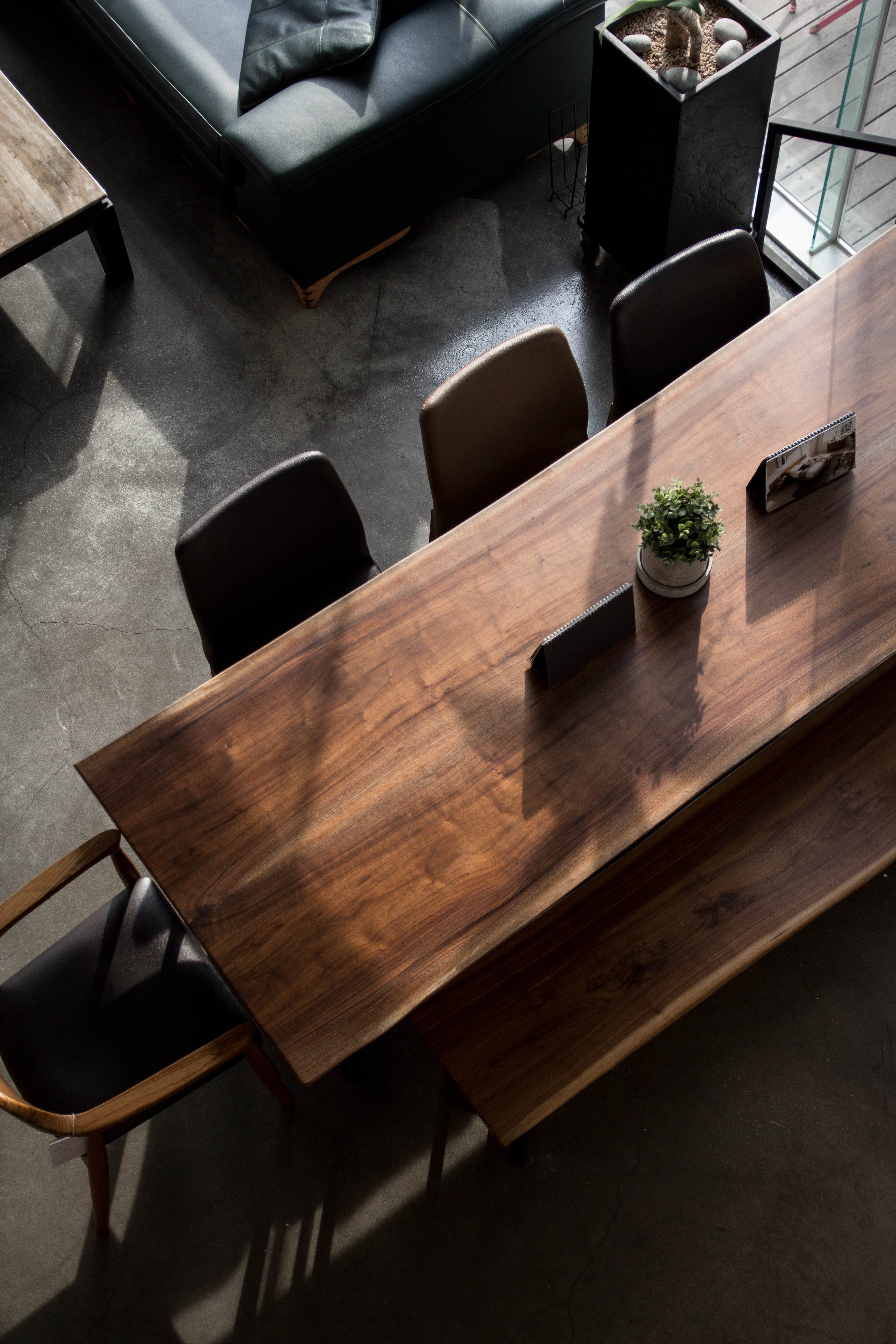 rectangular brown wooden table with white ceramic potted plant inside the room
