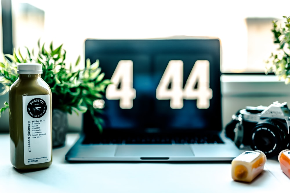 MacBook Pro displaying .4 44 beside camera and bottle