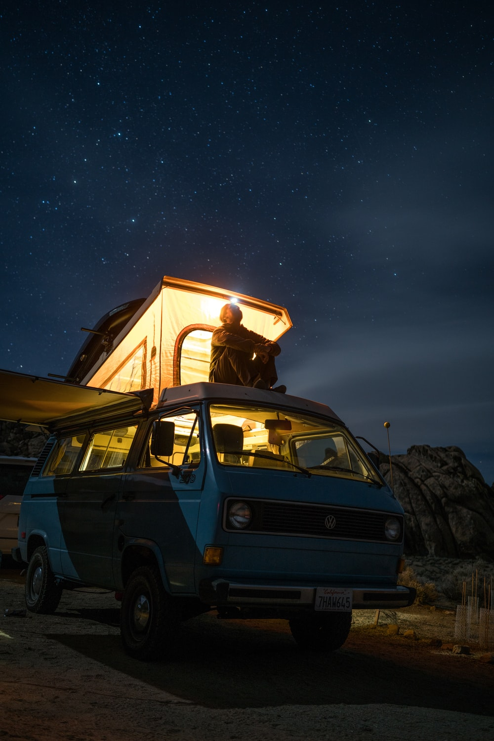 man sitting on top of blue van staring at sky during nighttime