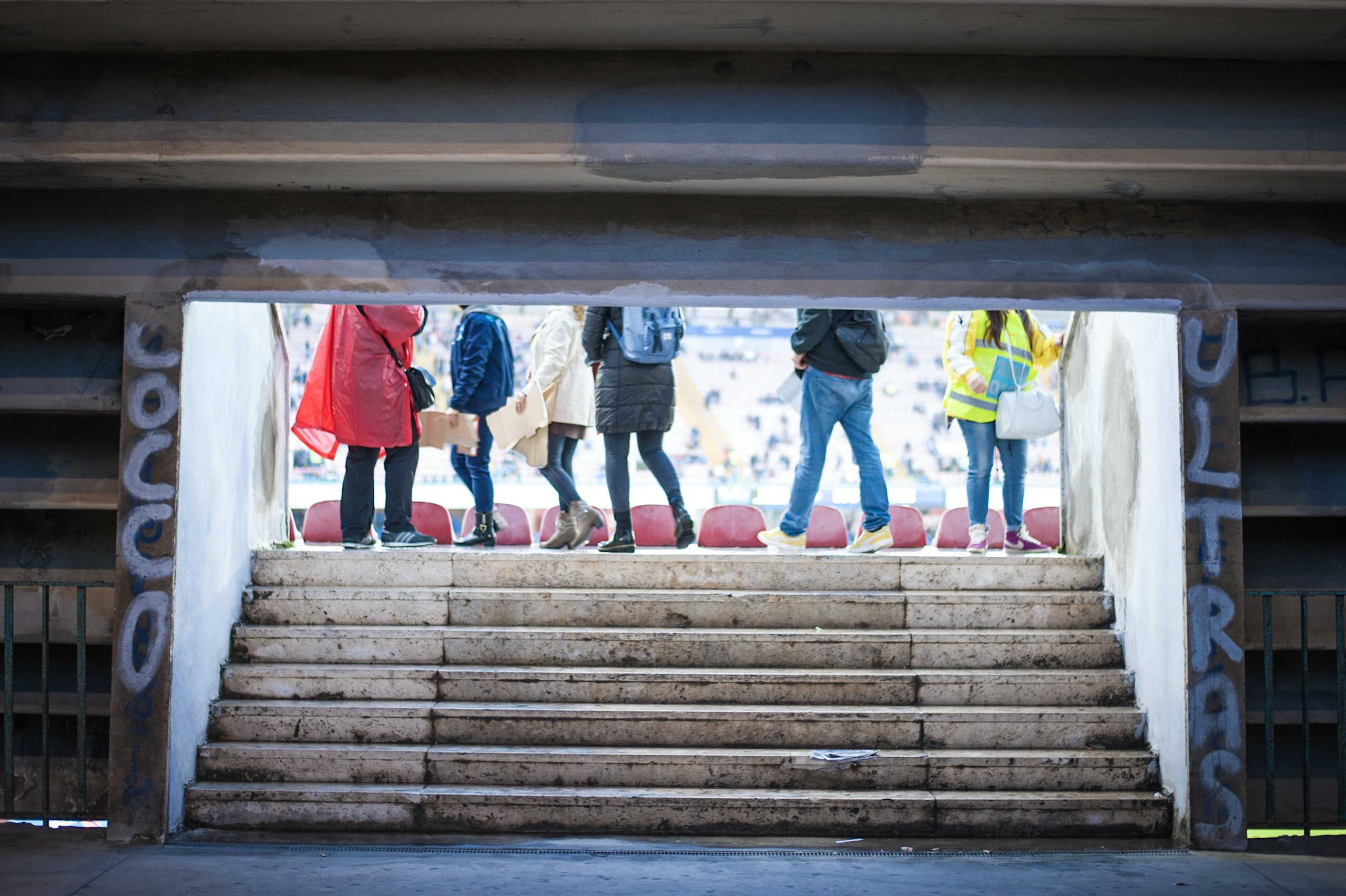 six person walking near tunnel