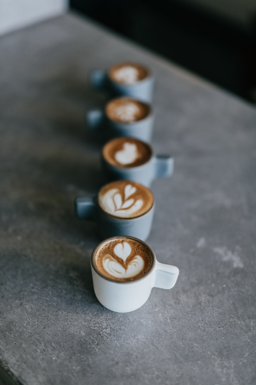 selective focus photography of white mug with latte forming heart