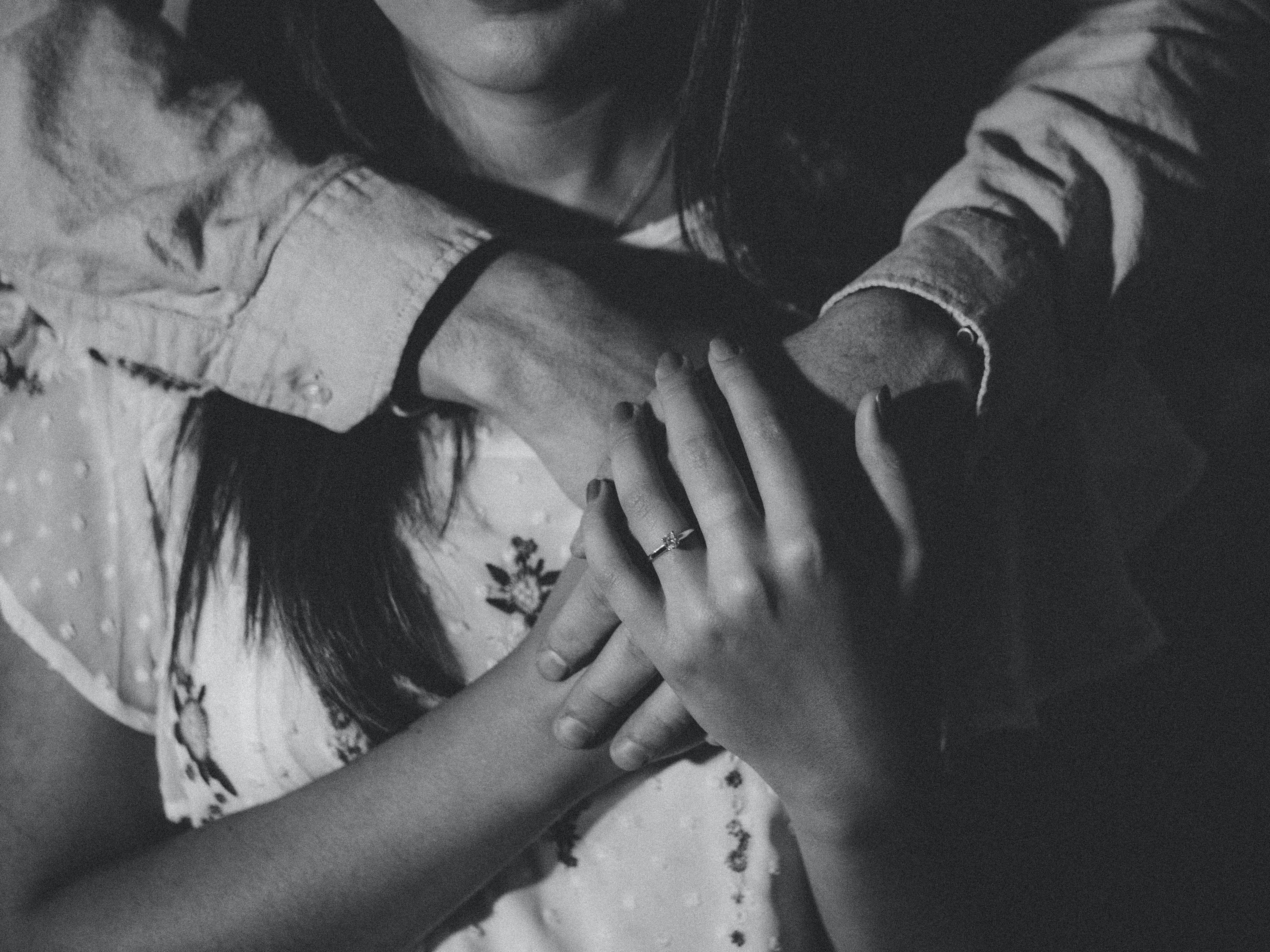 grayscale photography of woman holding her hands