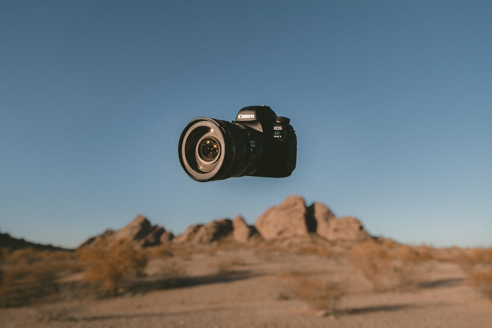 floating black Canon DSLR camera