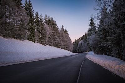 Winding road in winter wonderland at sunset