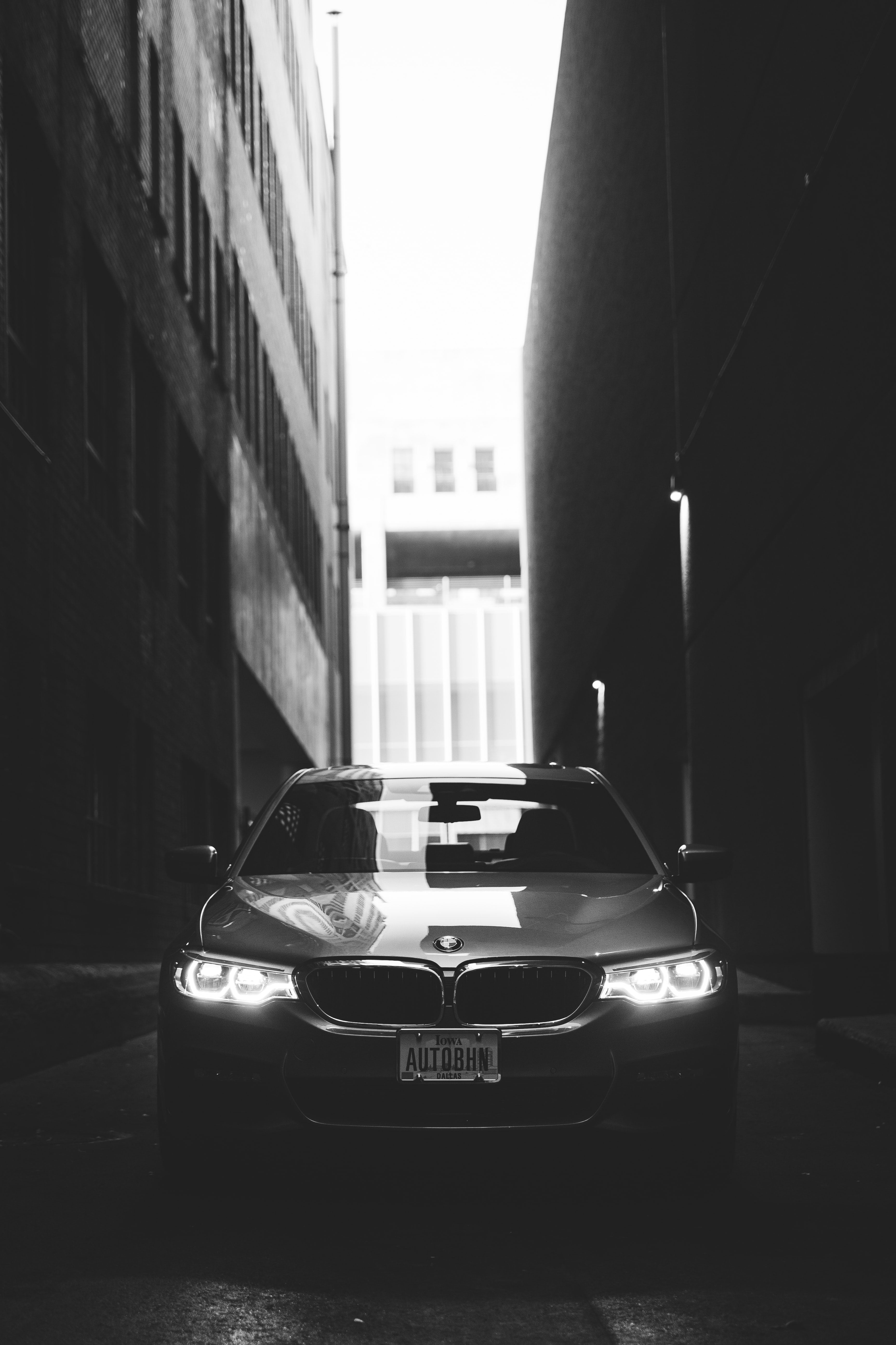 grayscale photo of BMW car parked between buildings