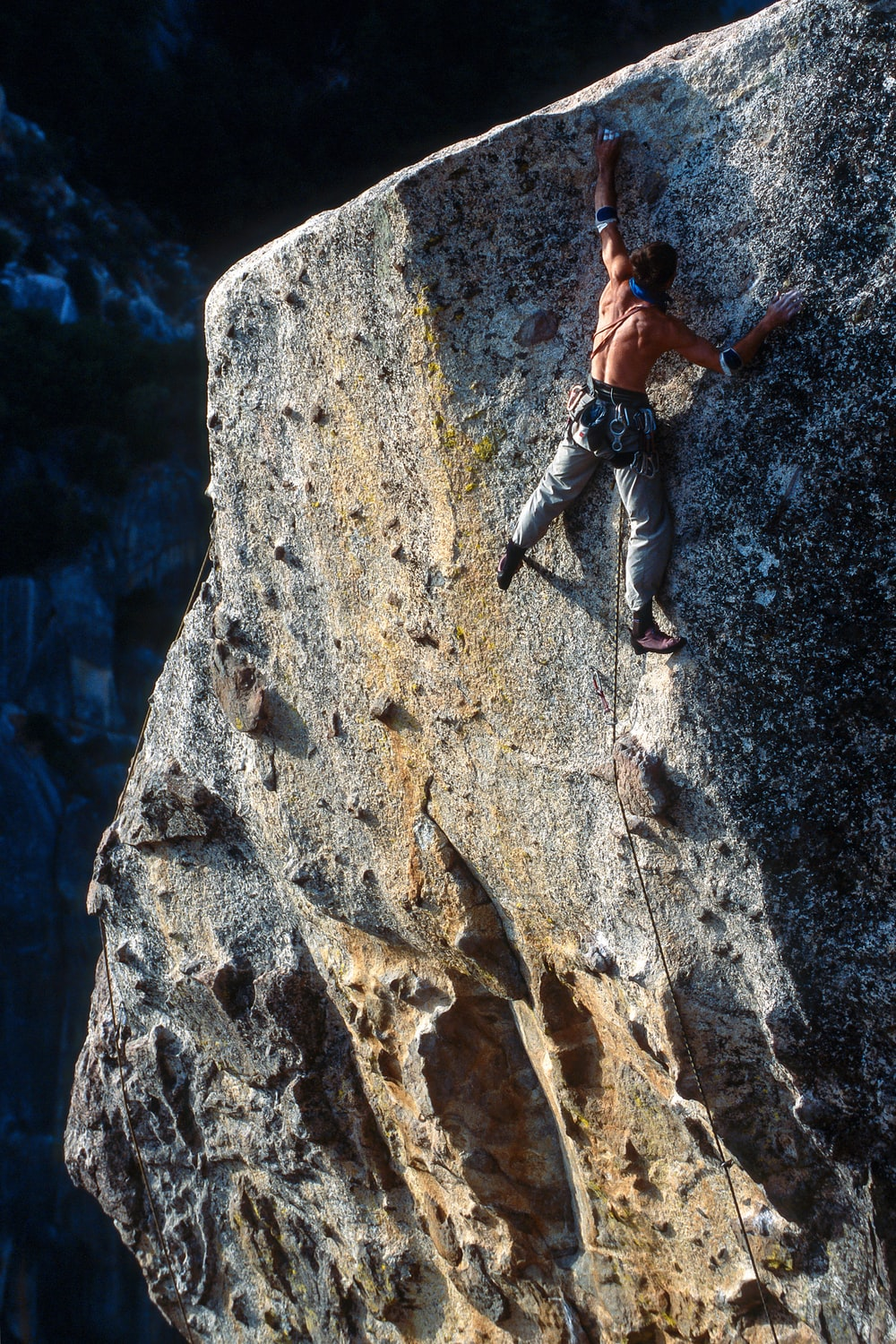 man climbing on rock hill during daytime