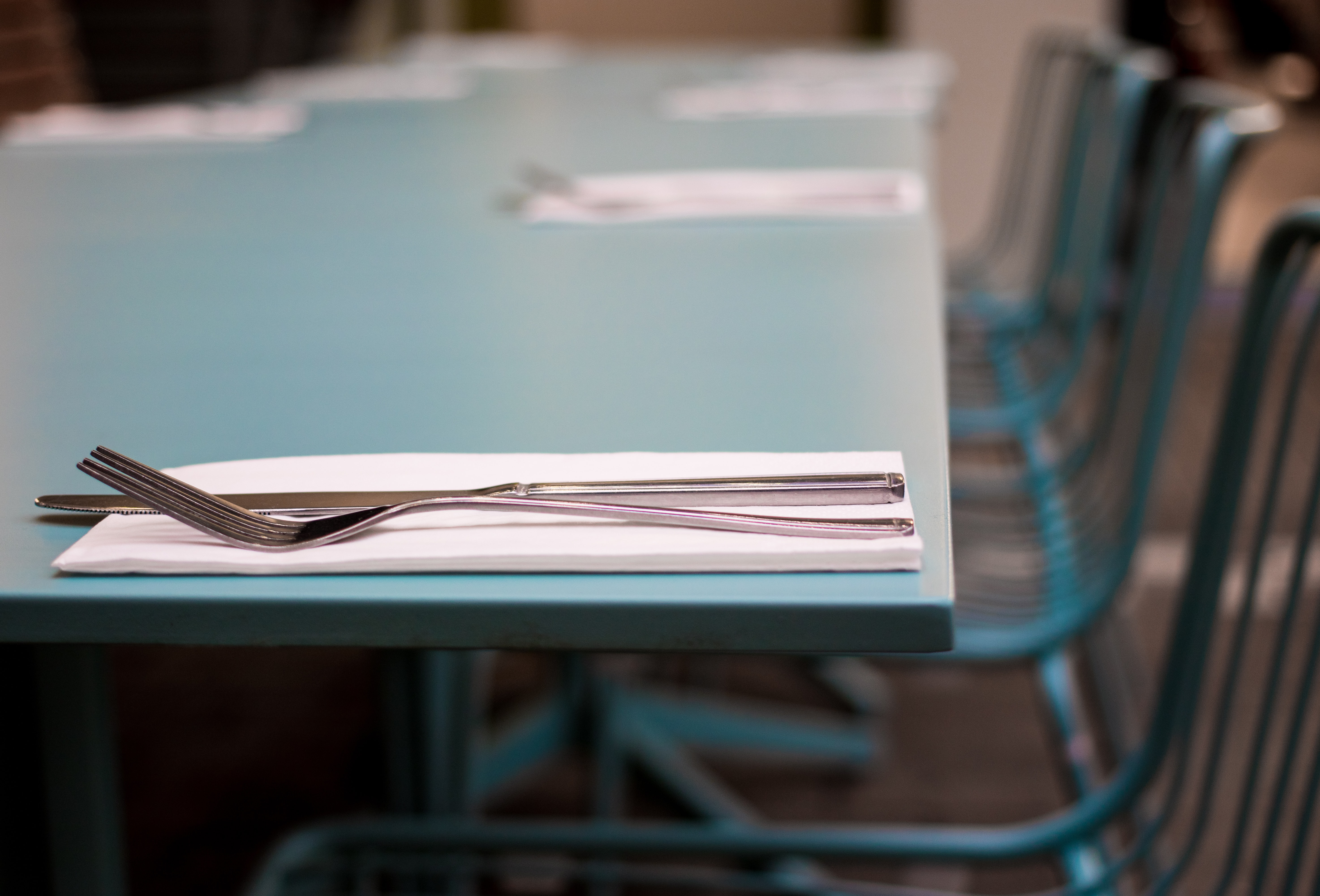 silver fork beside knife on green table selective focus photography
