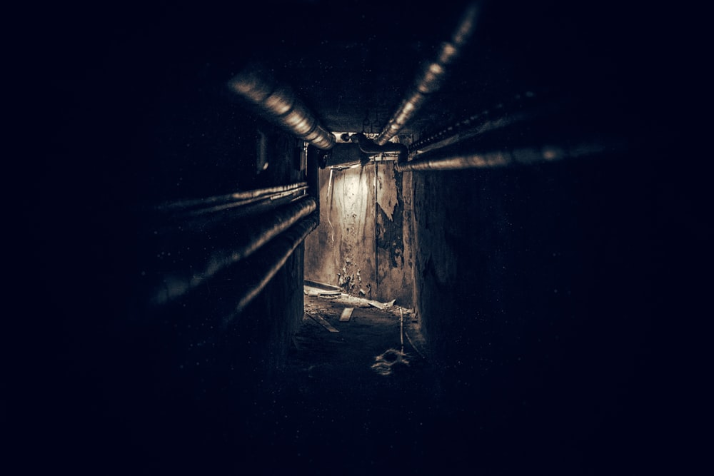 lighted brown tunnel with black metal pipes