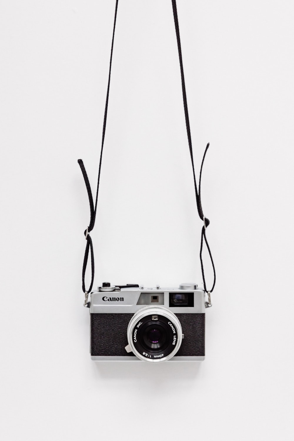 black and gray Canon camera on white surface