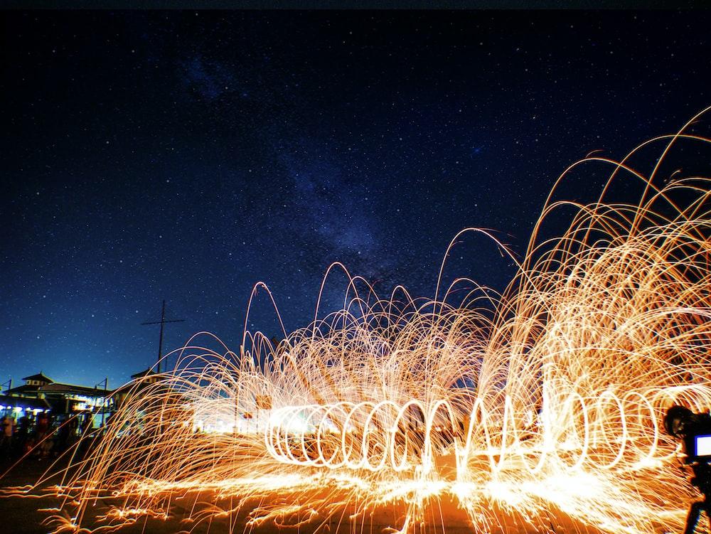 steel wool photography of spiral orange light at nighttime