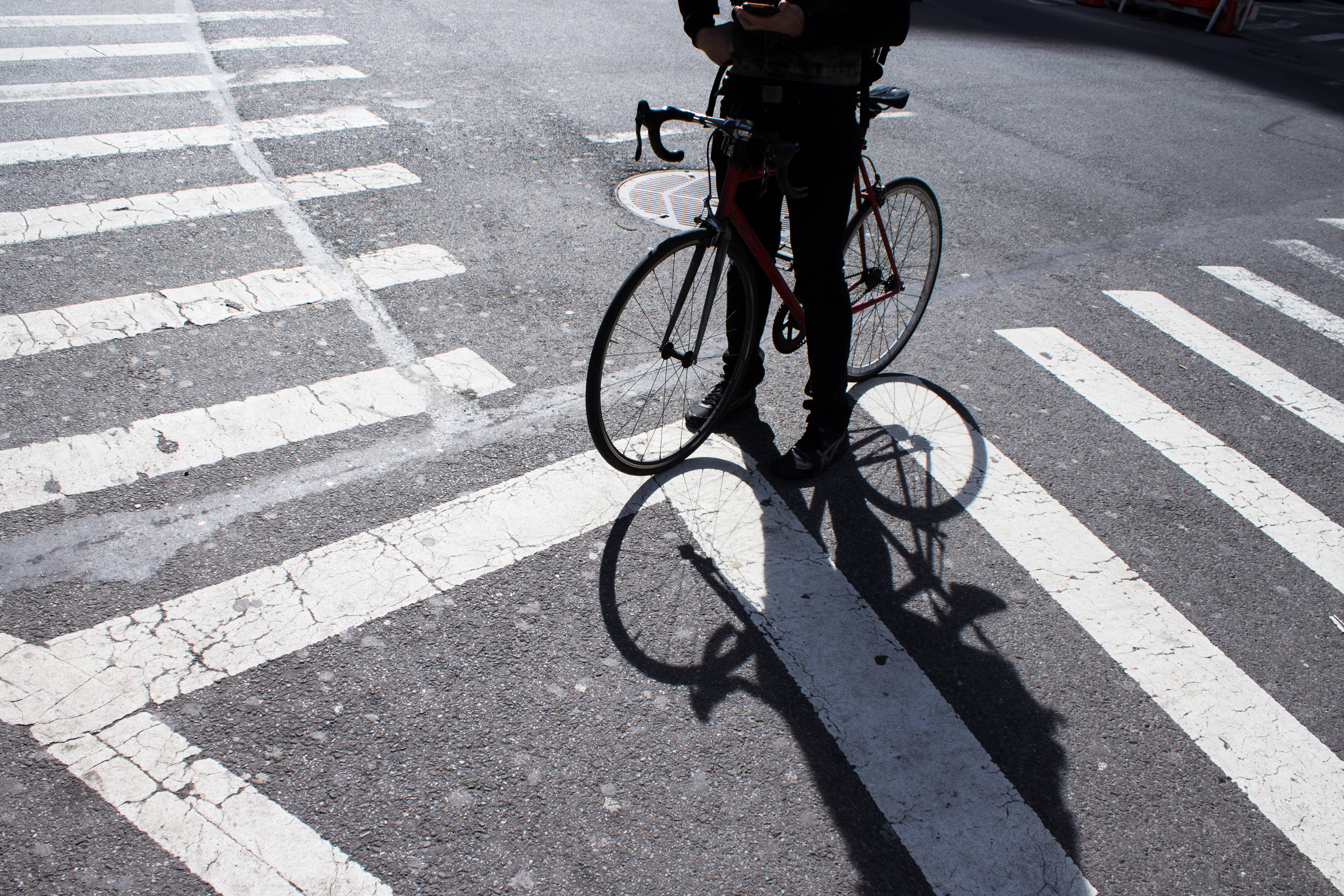 person with bicycle standing at pedestrian lane