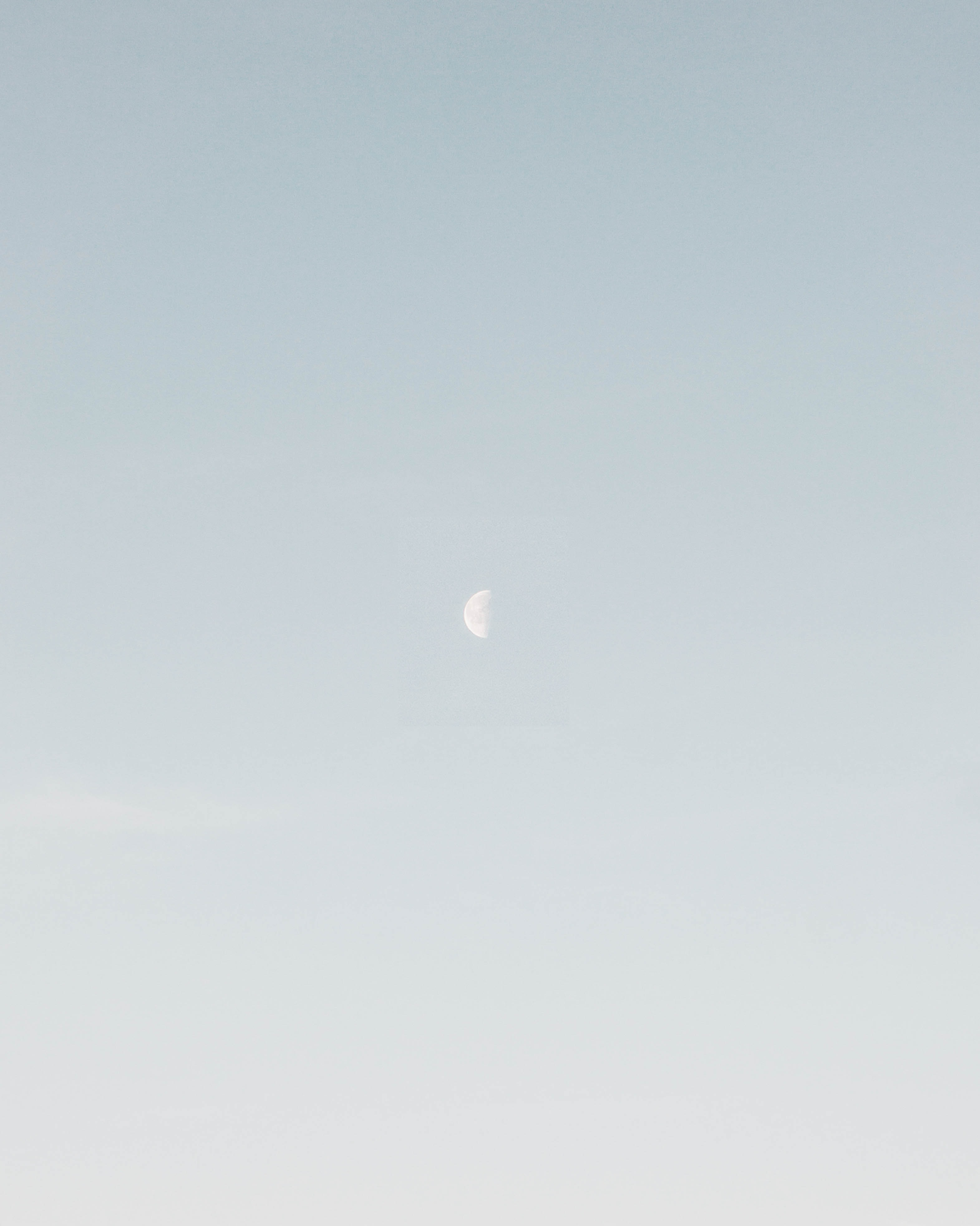 photo of half-moon during daytime