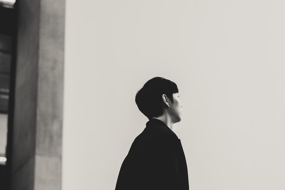 grayscale photography of person looking up while standing