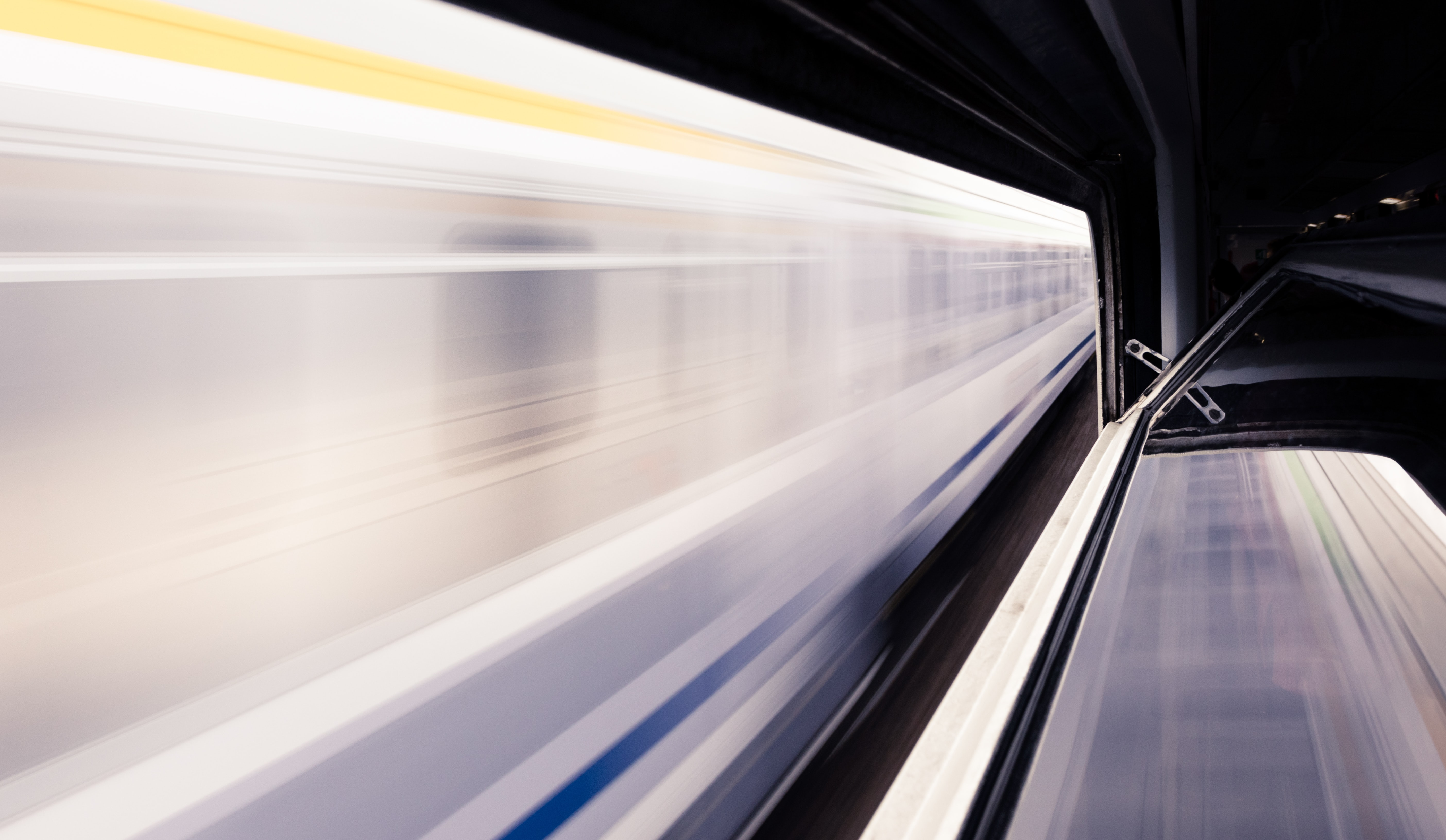 timelapse photo of white train and subway station