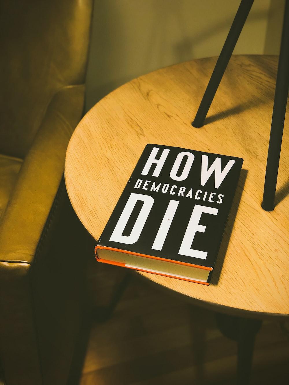How Democracies Die book on brown wooden side table
