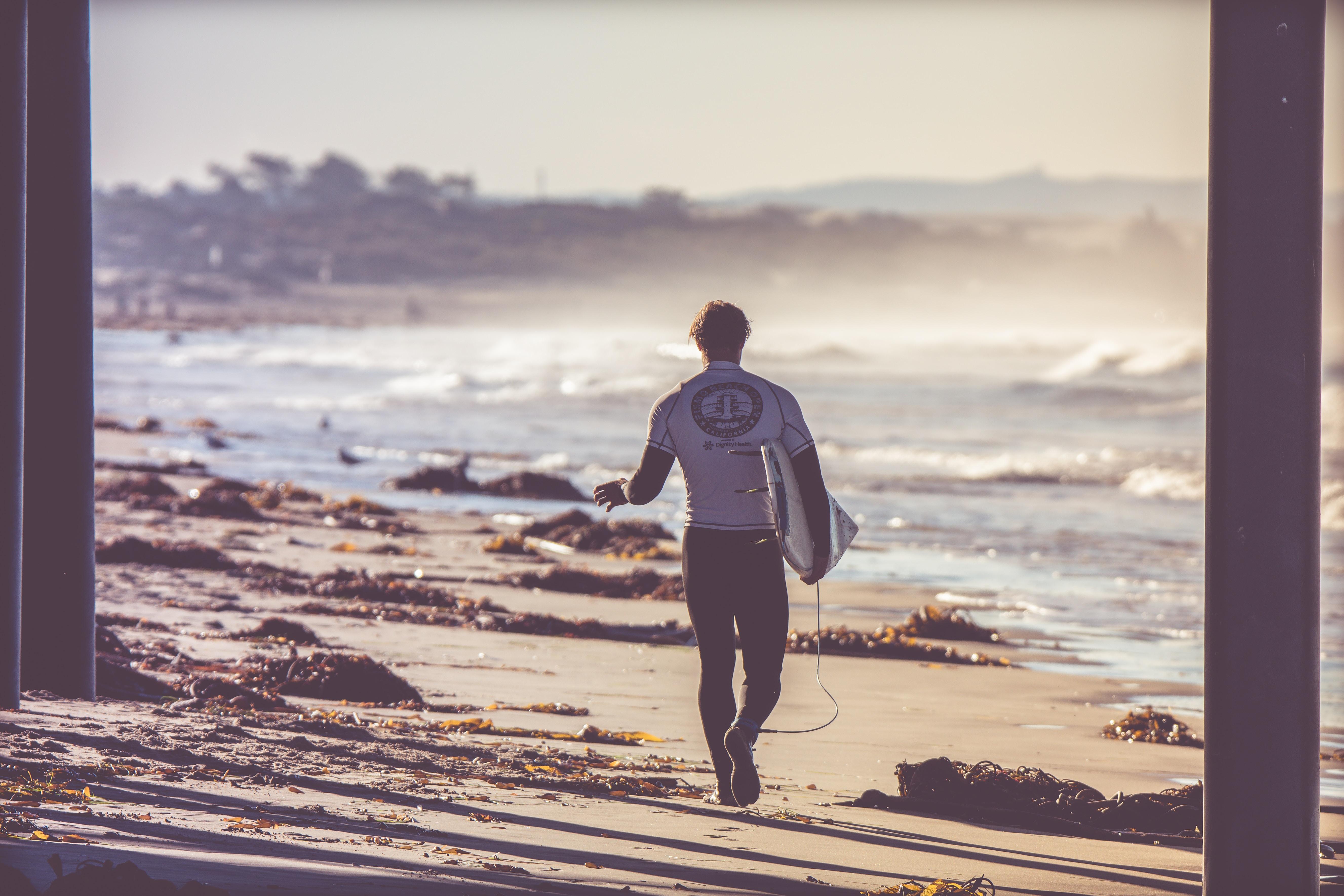 man carrying white surfboard walking towards beach