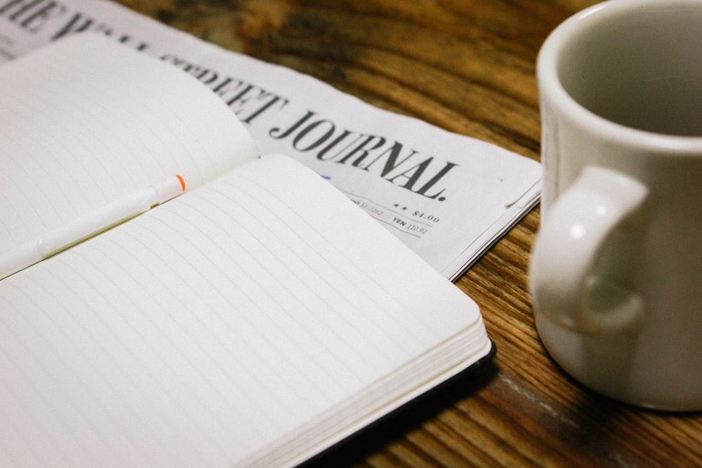 white ceramic mug near opened white notebook on brown wooden desk