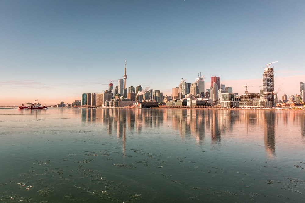 body of water and high rise buildings under blue sky