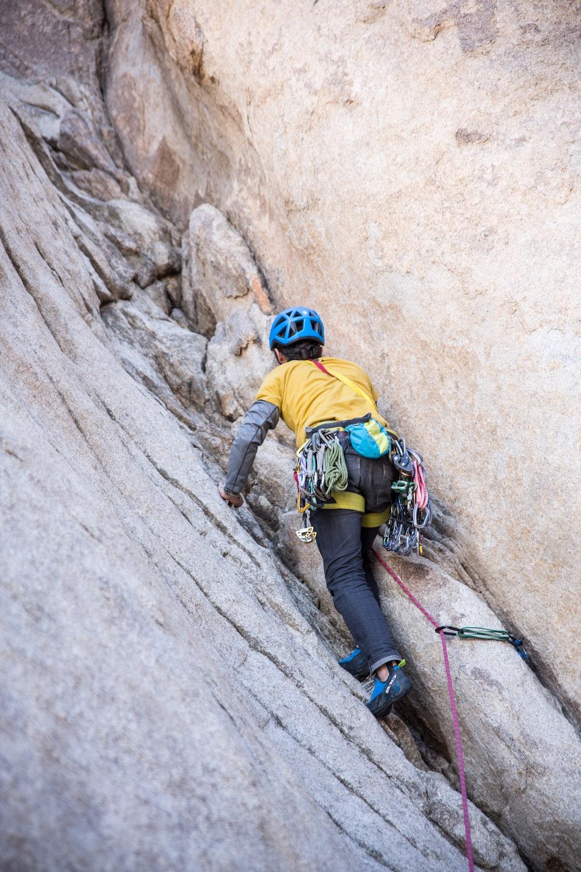 man wearing yellow climbing on cliff during daytime
