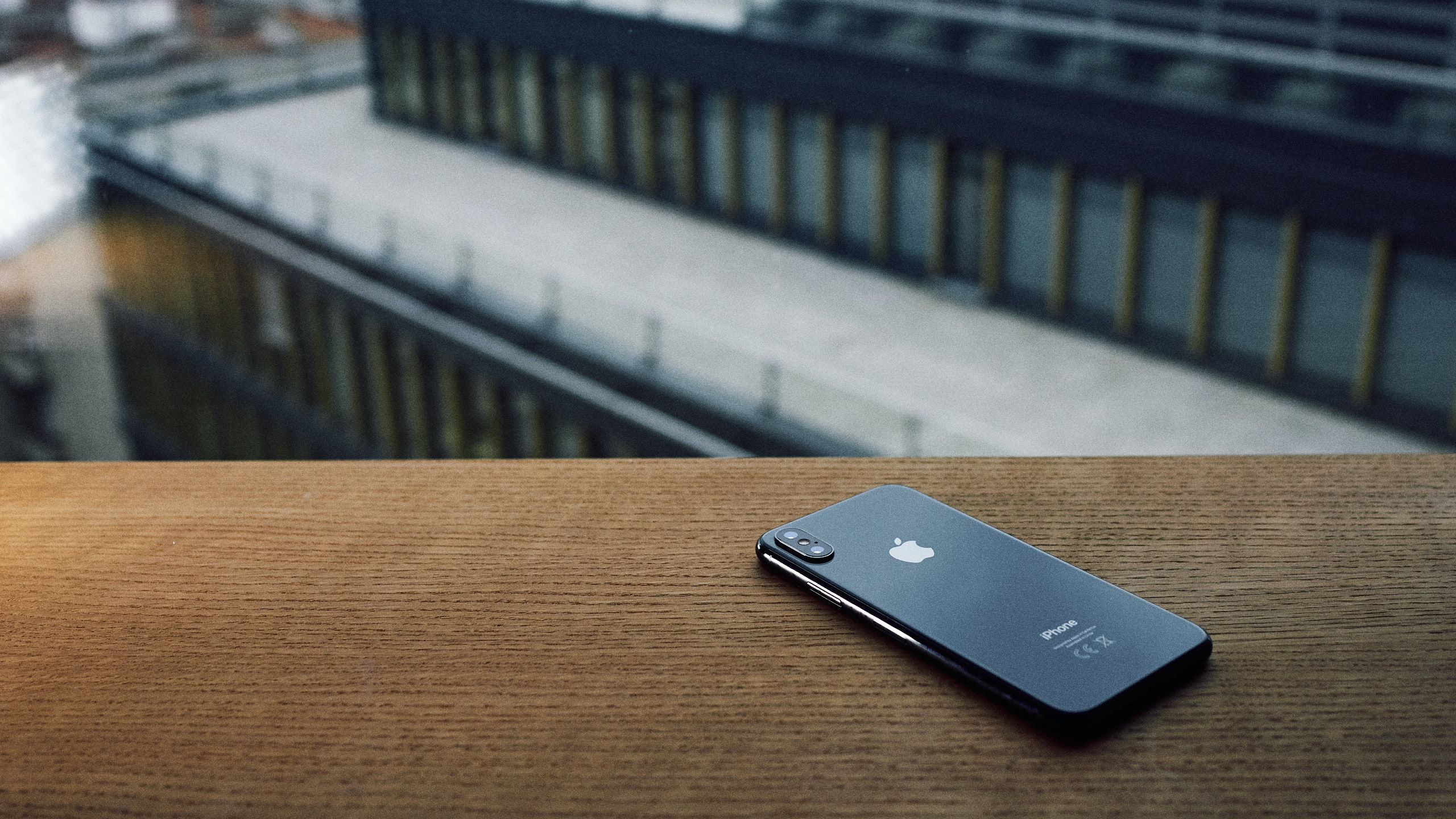 focus photo of space gray iPhone X on brown wooden table
