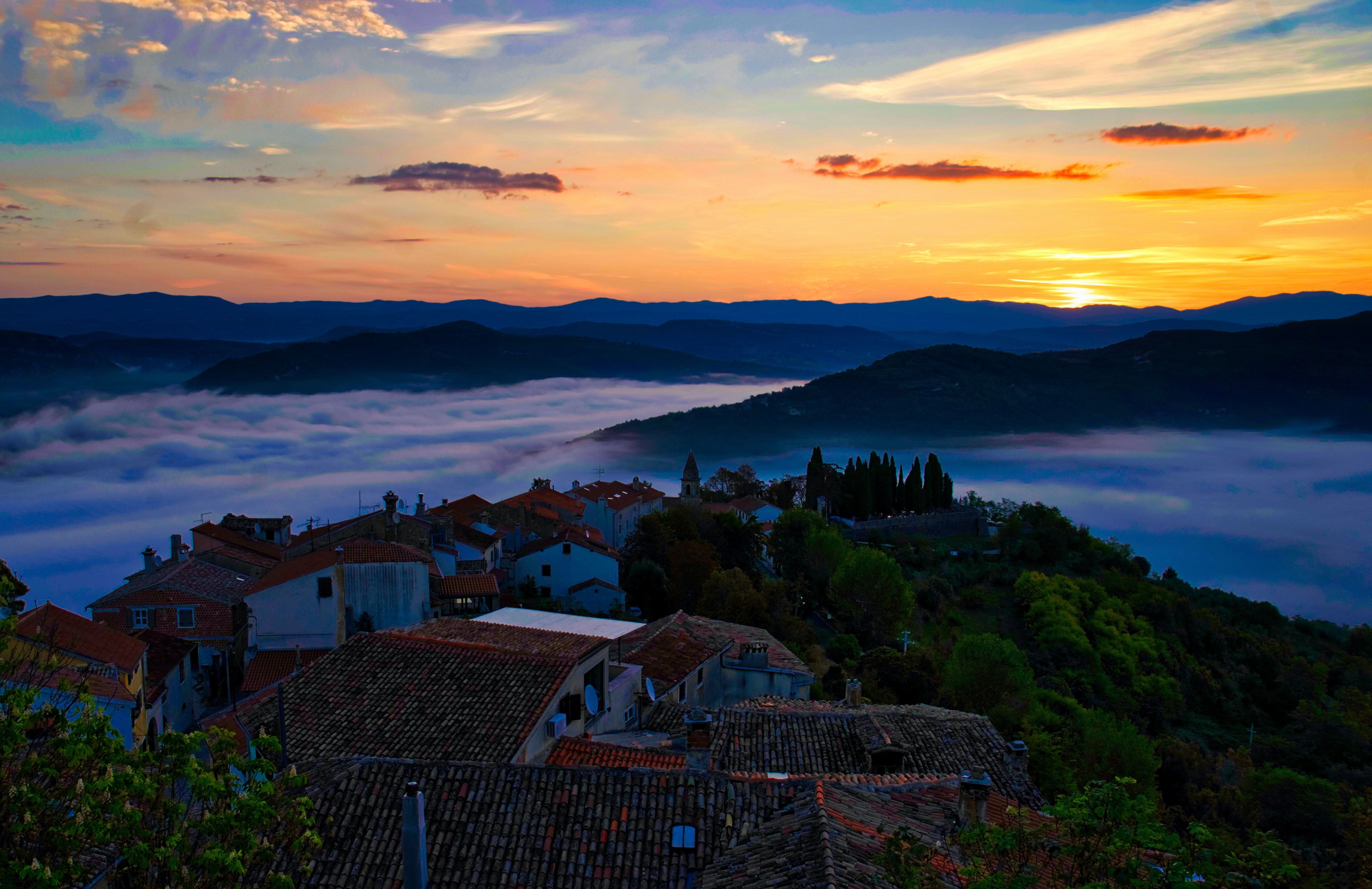 top view photography of village on top of hill covered with clouds under yellow skies