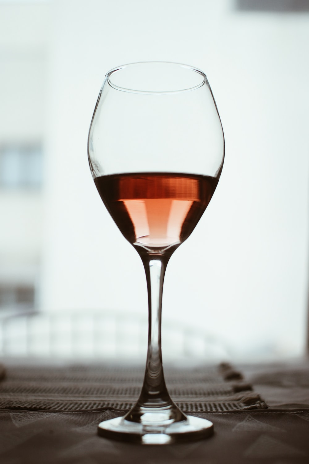 selective focus photography of clear long-stem wine glass
