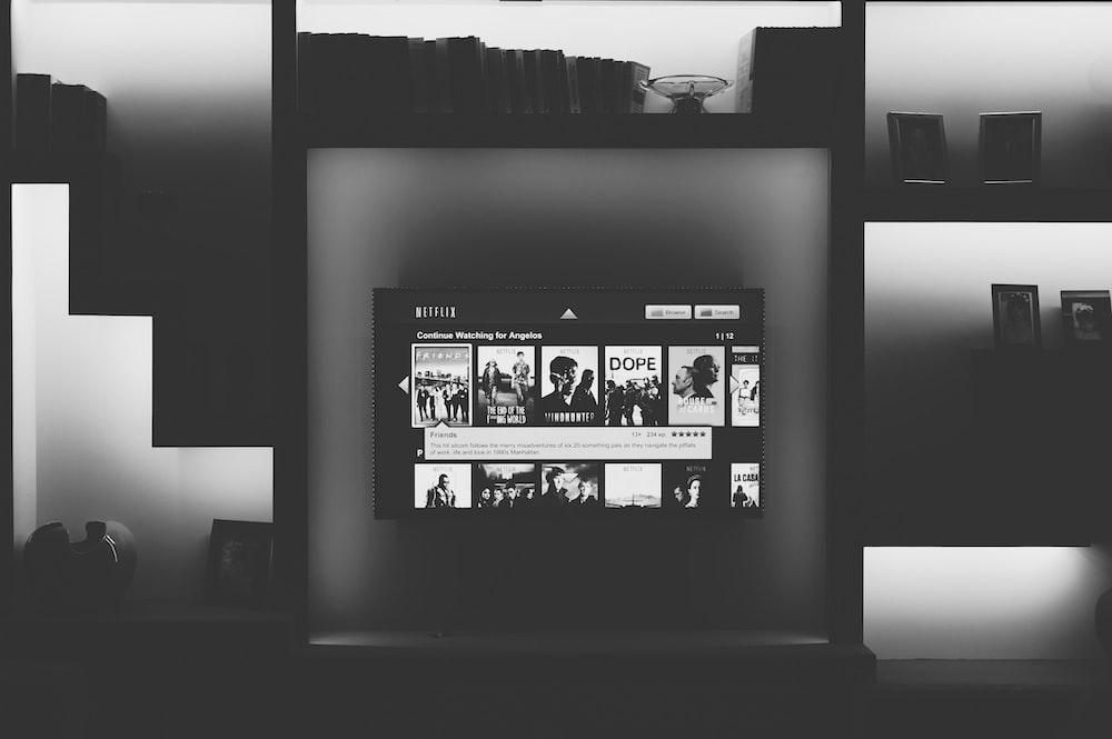 black flat screen TV mounted on shelf