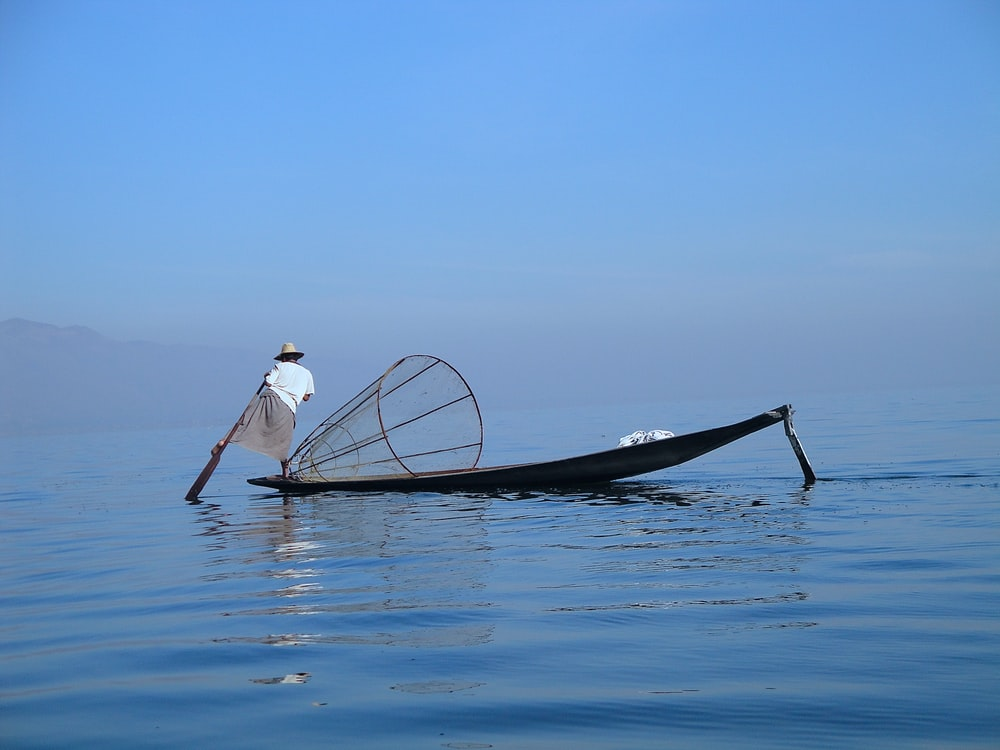 person standing on edge boat while fishing