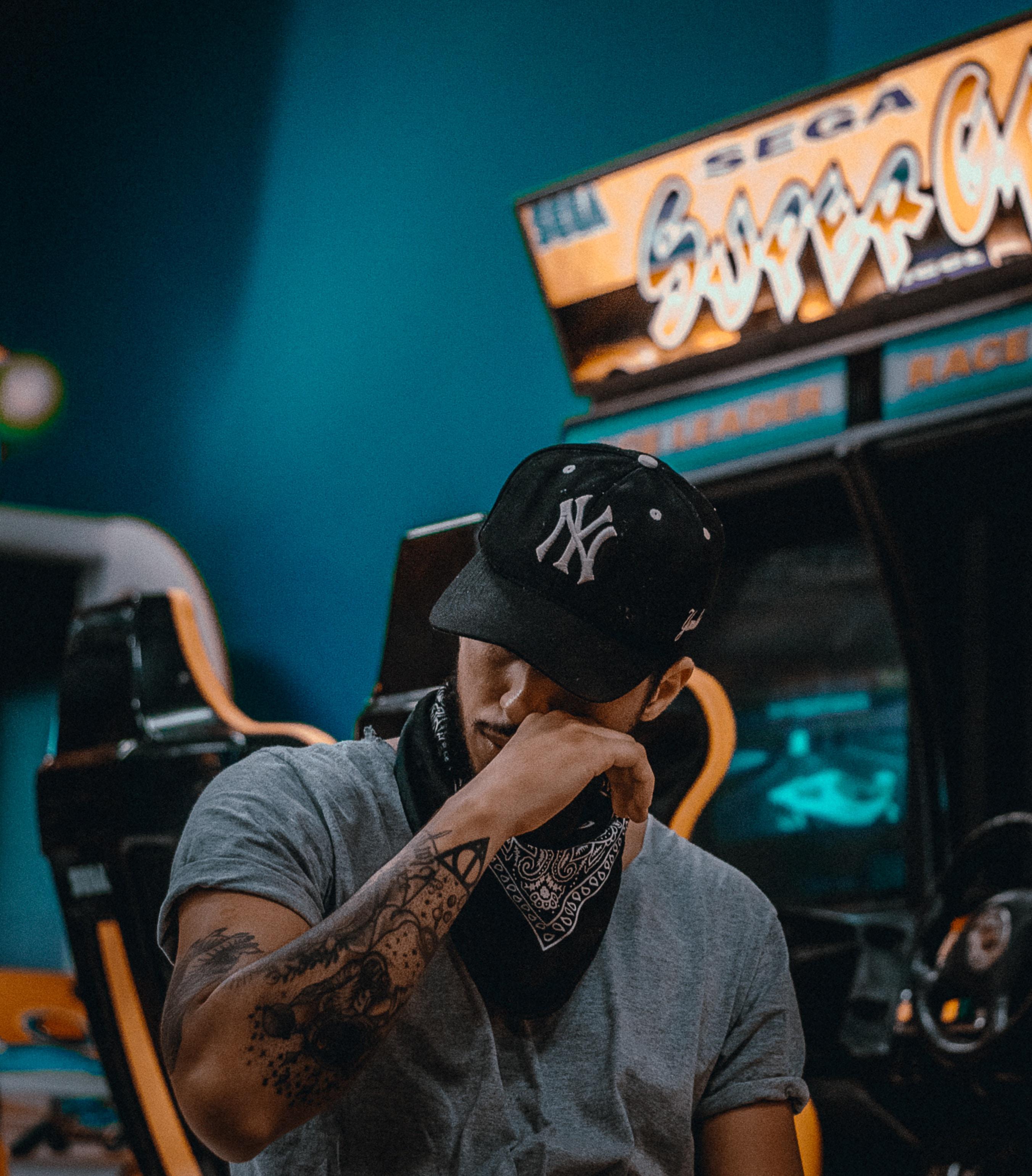 man sits near racing arcade machine