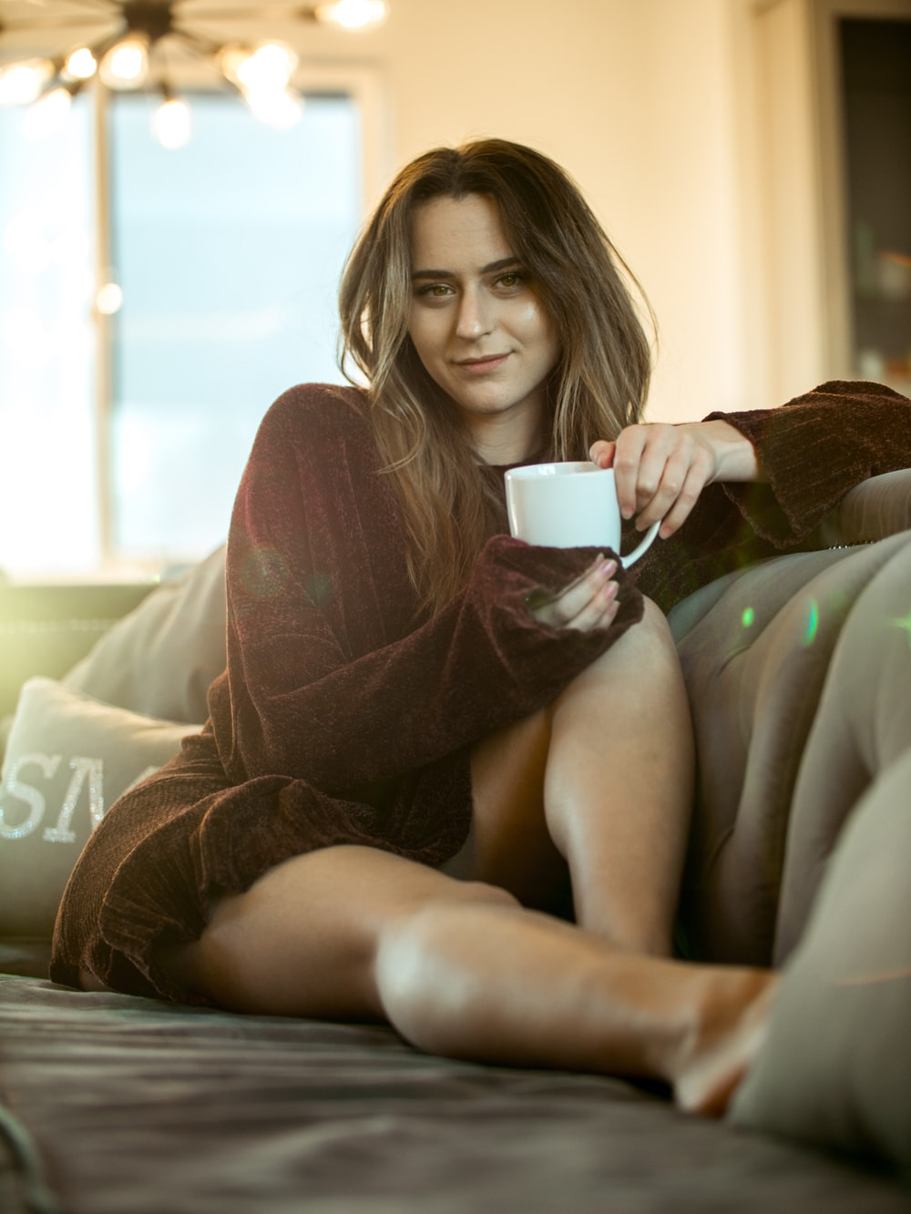 woman wearing maroon sweater sitting on sofa