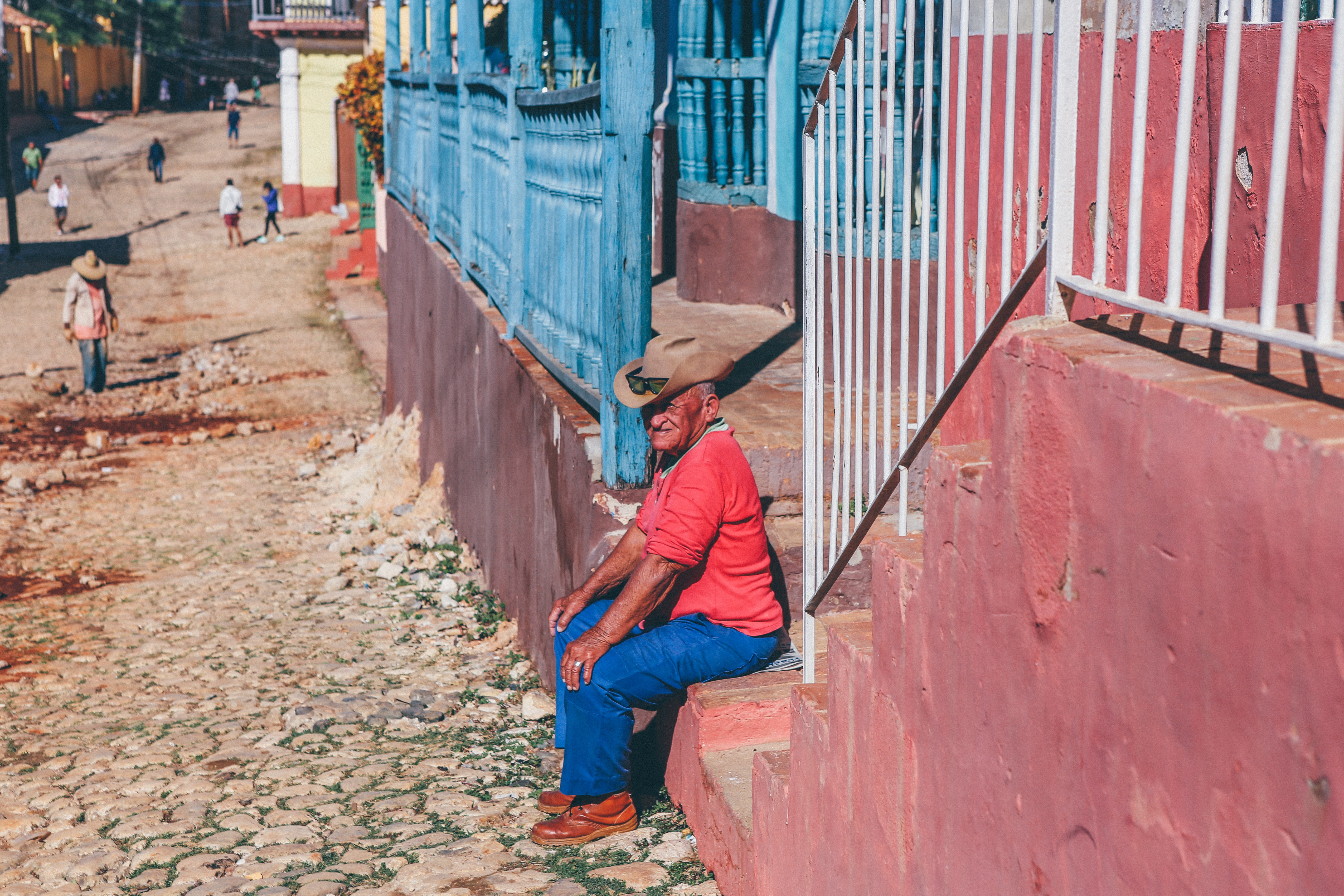 man sitting on red concrete stair in front of house during daytime