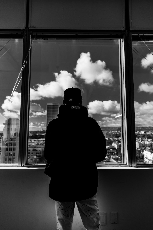 grayscale photo of man standing near window