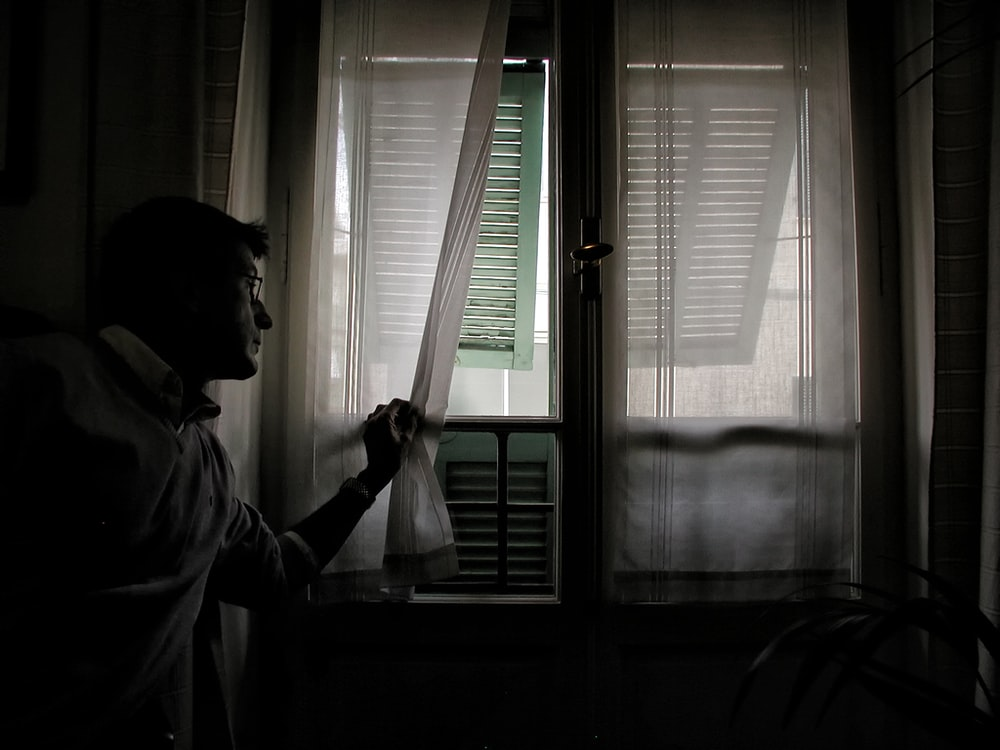 man holding white window curtain
