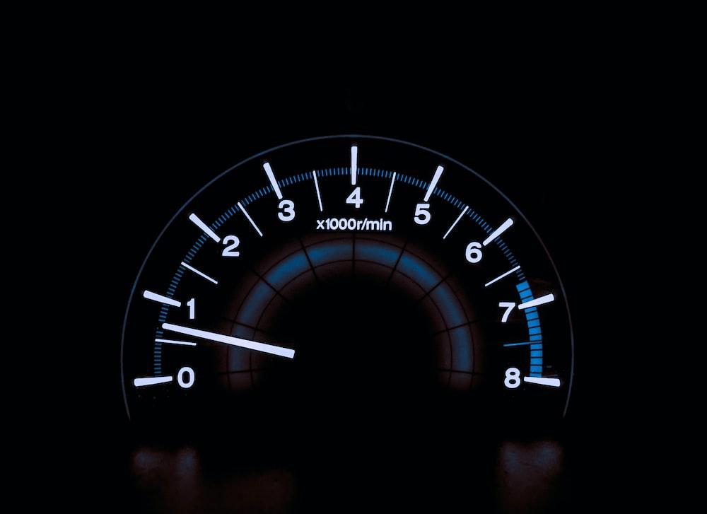 white and blue analog tachometer gauge