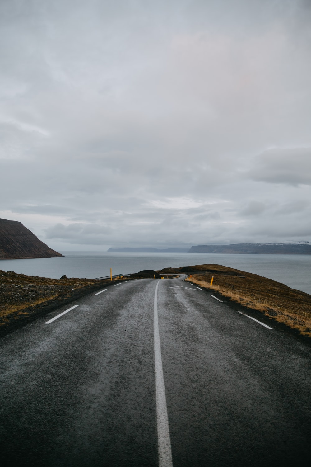 gray asphalt road going on the body of water