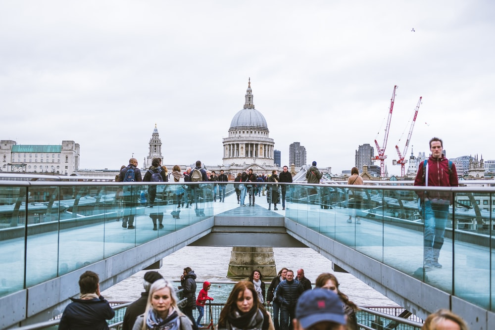 people on white bridge with blue glass rails near white domed building during daytime