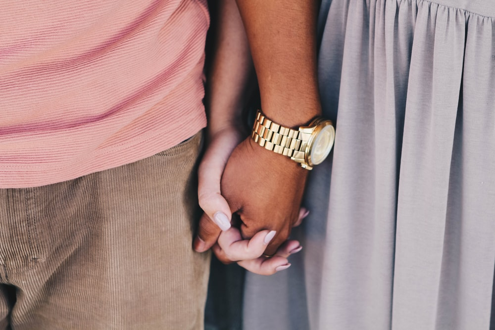 girl and boy holding hands white boy wearing gold-colored watch