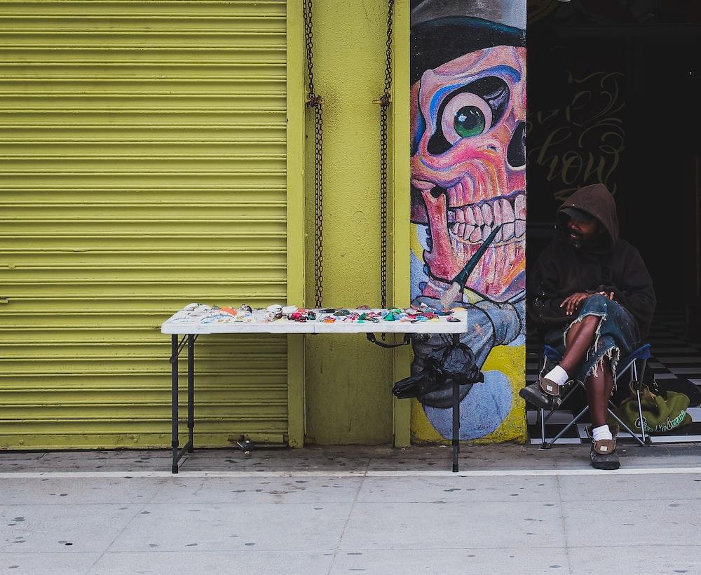 man in brown hoodie sitting beside table
