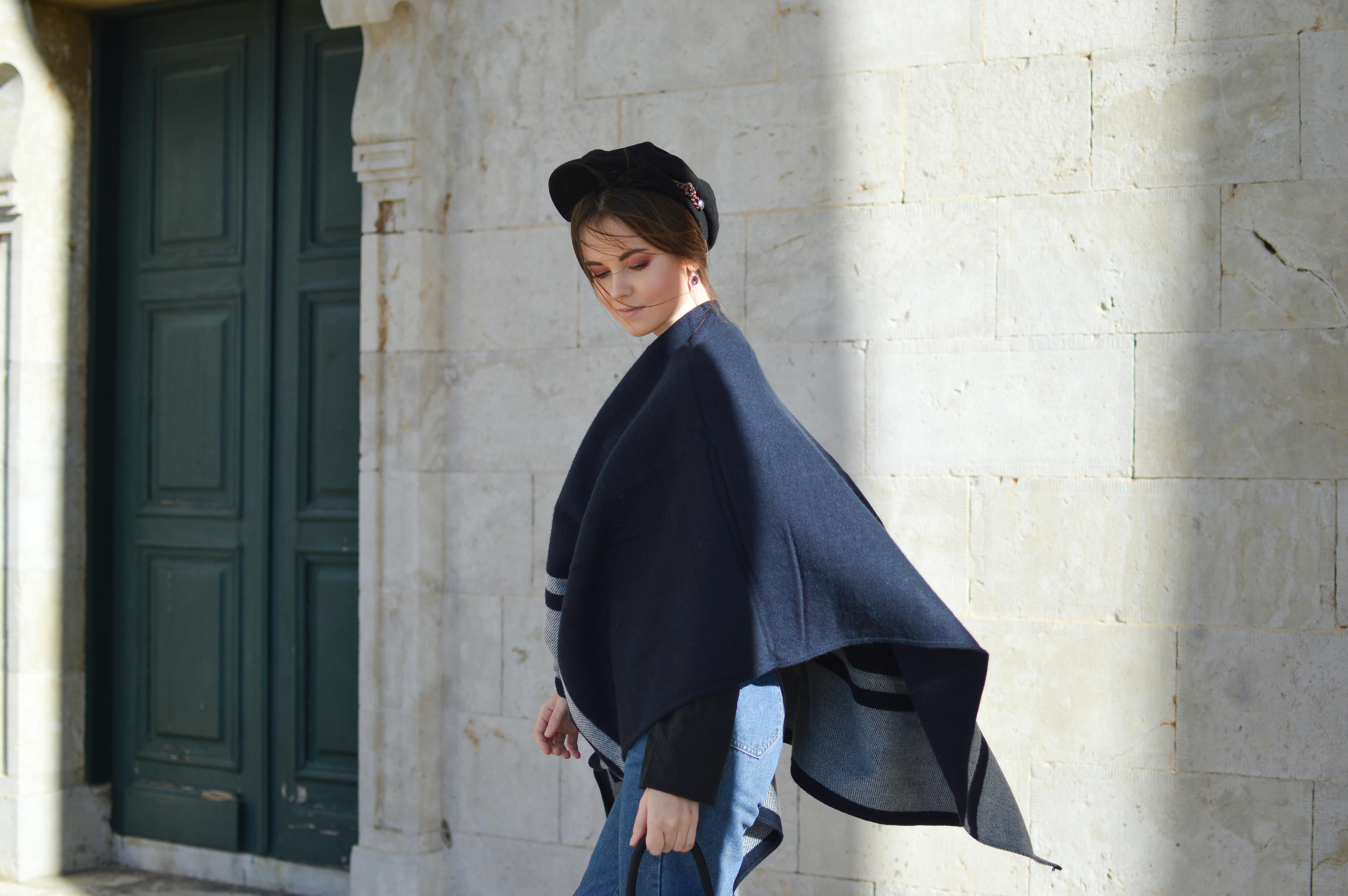 woman wear black scarf posing near wall