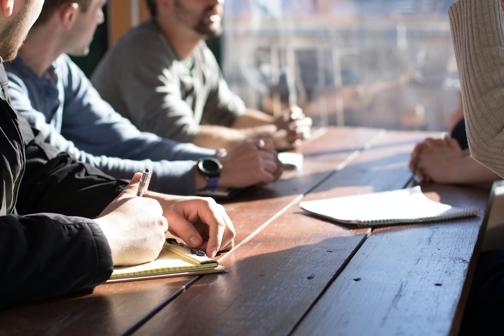 people sitting on chair in front of table while holding pens during daytime