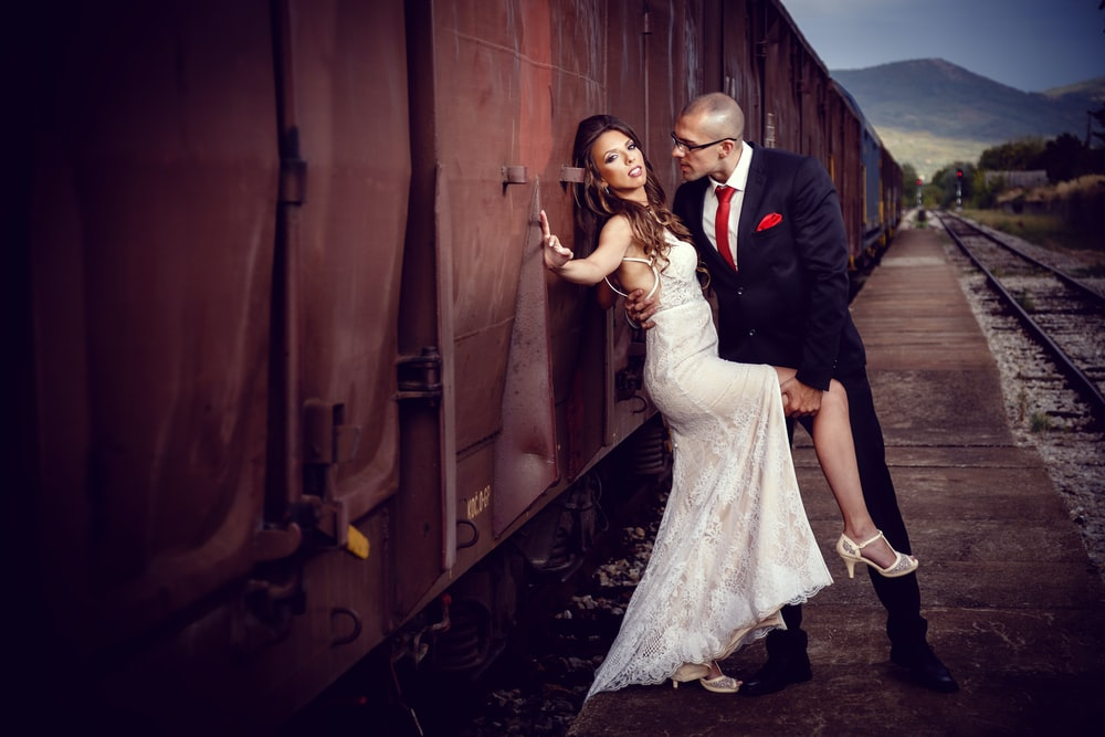 bride and groom beside train during daytime